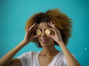 A young woman holding Bitcoins up to her eyes