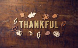 "A bronze tone ""Thankful"" amidst leaves, pumpkins and acorns."