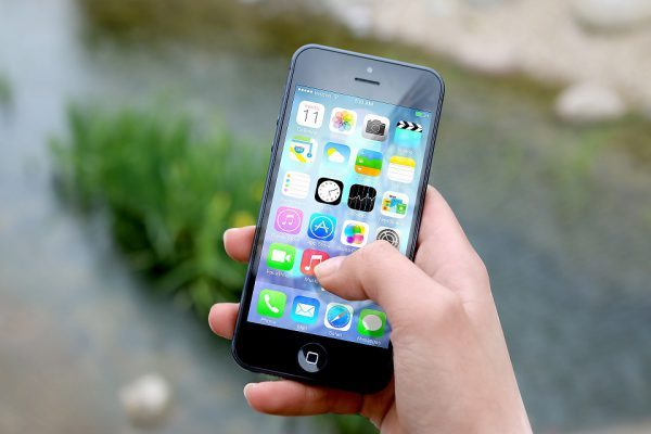 A hand holding a cell phone with the Apps page showing.