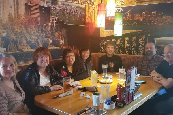 7 members of the Bellevue branch of ITsoft seated around a large dining table.
