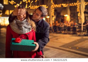 Man covering woman's eyes with one hand and holding a package wrapped in green giftwrap topped off with a red bow..