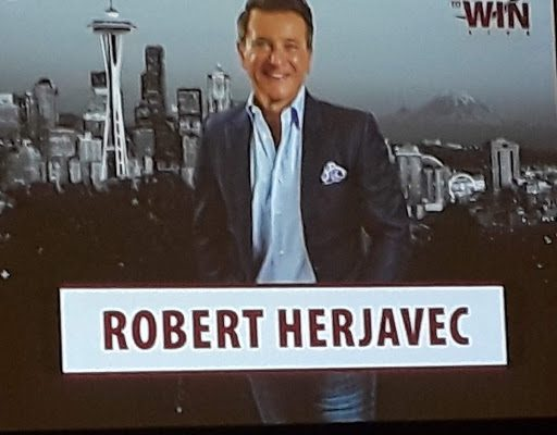 Photo of an overhead picture of Robert Herjavec with the Space Needle and Seattle skyline as a background.