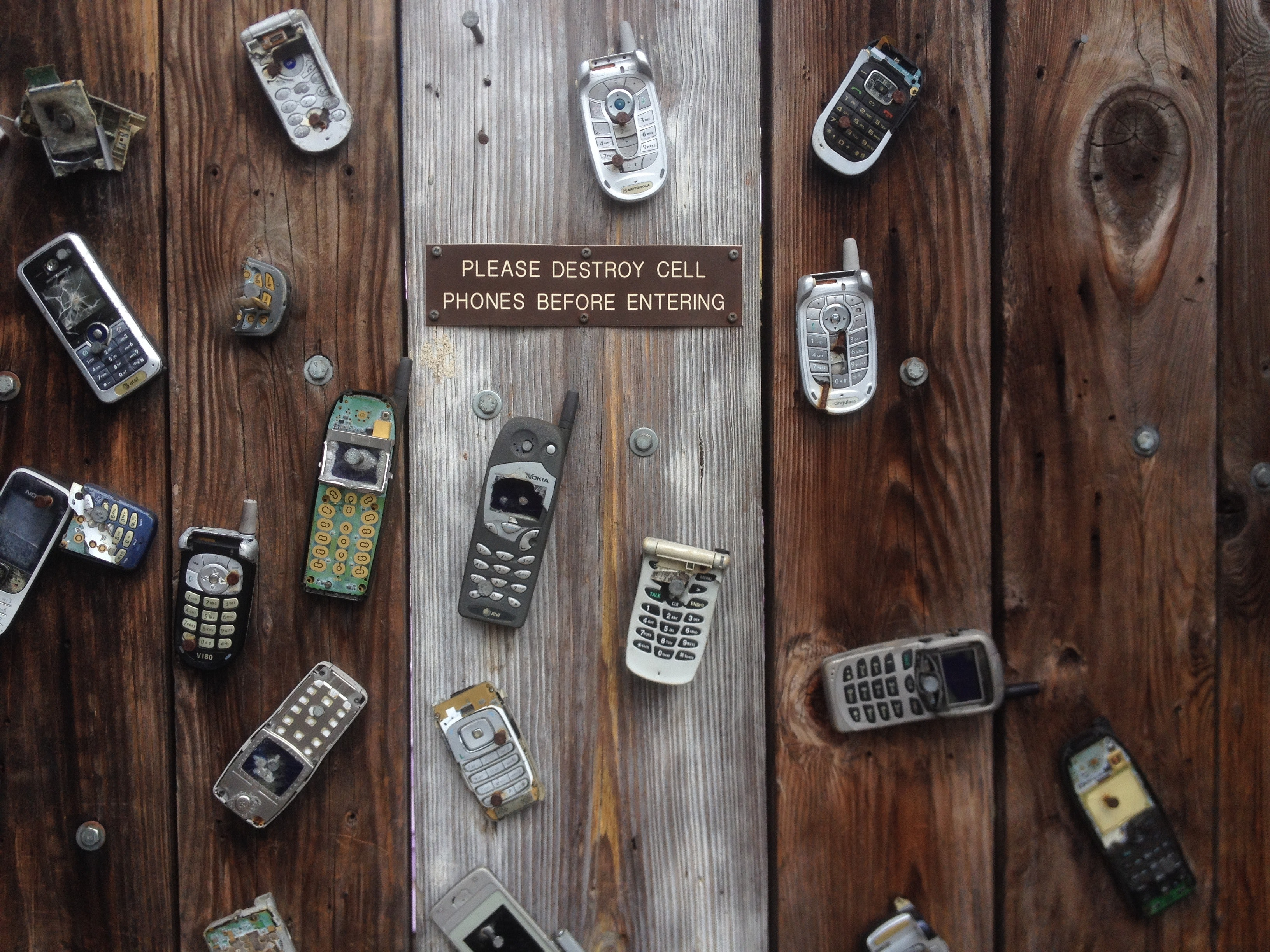 19 very old cell phones on pieces of weathered wood with a sign that says: Please Destroy Cell Phones Before Entering.