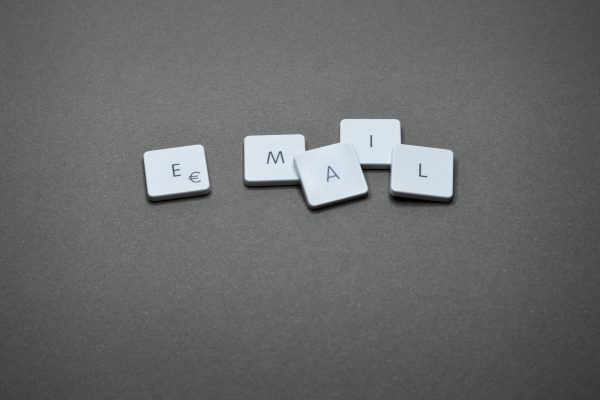 """The letters """"e"""", """"m"""", """"a"""", """"i"""", """"l"""" placed on individual white tiles spelling out the word email on a gray-tone background."""