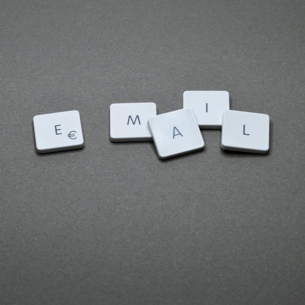 "The letters ""e"", ""m"", ""a"", ""i"", ""l"" placed on individual white tiles spelling out the word email on a gray-tone background."