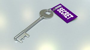"A silver skeleton/master/passkey has a purple tag attached to it with the word, ""SECRET"" attached."