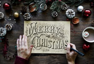 """A Calligrapher holding a pen. With a beautiful hand-lettered plaque saying, """"Merry Christmas"""".  It is placed on top of a background with snow-dusted pine cones and a mug of hot cocoa with a smiling faced marshmallow."""